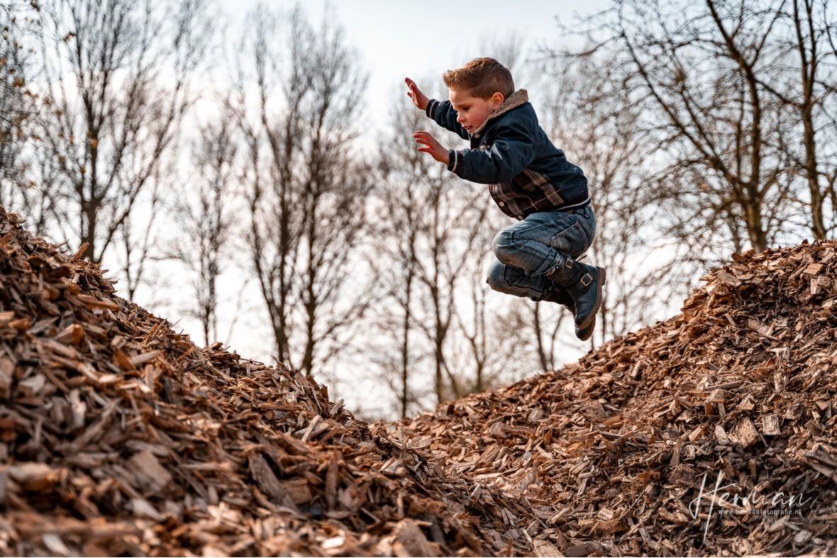 Lifestyle fotoshoot - Jongetje speelt in berg met houtsnippers in Rotterdam - Herman Fotografie