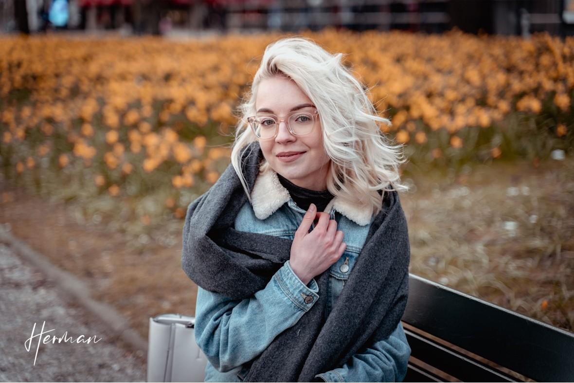 Polyna op een bankje voor een veld met narcissen in Den Haag - Portret fotoshoot in Den Haag