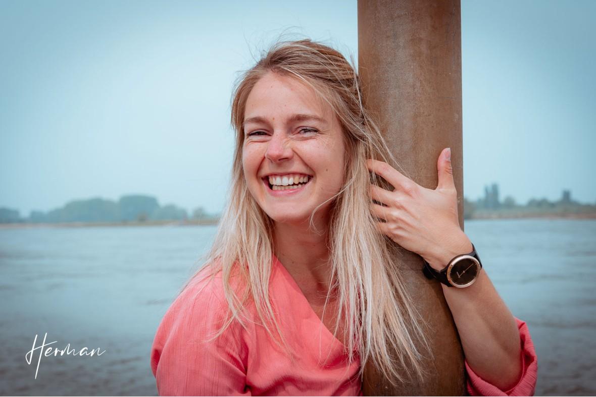 Claudia knuffelt een paal aan de Waal - Portret fotoshoot in Zaltbommel